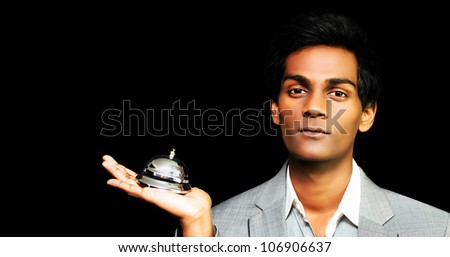 Asian hotel Bellboy holding bell on black background - stock photo