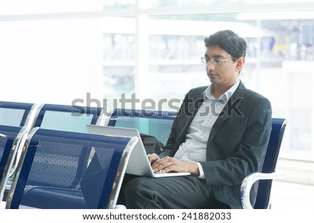 Asian Indian business man waiting his flight at airport, sitting on chair and using laptop. - stock photo