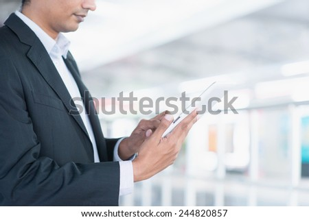 Asian Indian business people using tablet computer while waiting train at railway station.  - stock photo