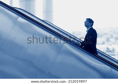 Asian Indian businessman going up escalator, side view in blue tone. - stock photo
