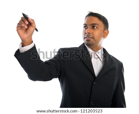 Asian Indian businessman in black suit writing something on glass board with marker - stock photo
