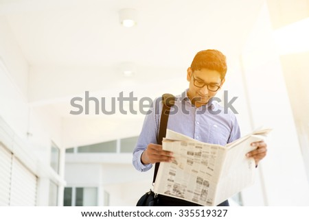 Asian Indian businessman reading newspaper on the way to work in a morning. Handsome male model. - stock photo