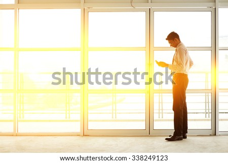 Asian Indian businessman using mobile phone in modern office building, golden sunset background. - stock photo