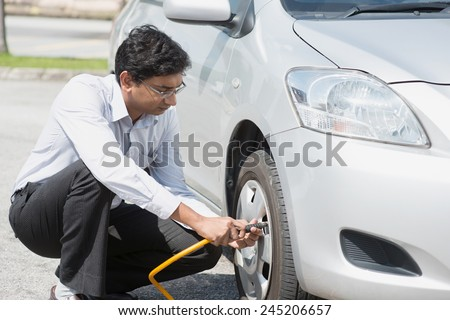 Asian Indian driver checking air pressure and filling air in the tires of his car. - stock photo