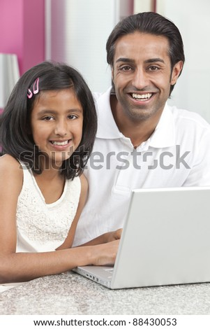 Asian Indian father and daughter, man and girl, using laptop computer in the kitchen at home - stock photo