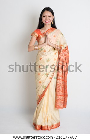 Asian Indian girl in a greeting pose, traditional sari costume, full length standing on plain background - stock photo
