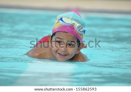 Asian Indian kid in swimming pool in a Arab resort - stock photo
