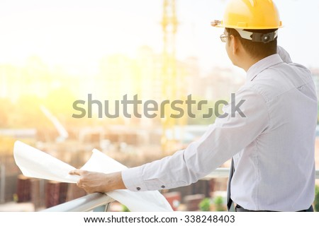 Asian Indian male site contractor engineer with hard hat holding blue print paper looking away inspecting progress at construction site, crane with golden sunlight at the background. - stock photo
