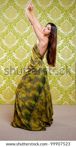 Asian Indian woman dancing full length with ethnic dress on green wallpaper - stock photo
