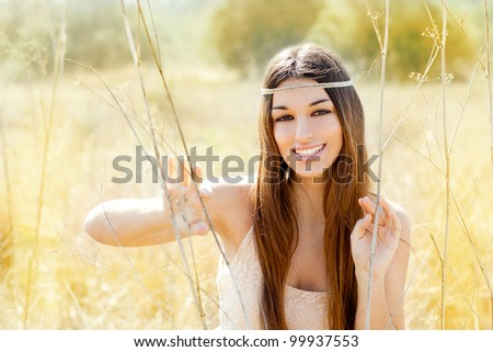 Asian indian woman portrait in golden dried grass field - stock photo
