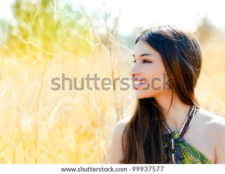 Asian indian woman profile portrait in golden grass field - stock photo