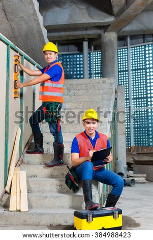 Asian Indonesian builder or craftsman with hardhats, checklist and a bubble level controlling or checking a walls of a tower building or construction site  - stock photo