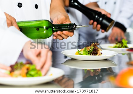 Asian Indonesian chef along with other cooks in restaurant or hotel commercial kitchen cooking, finishing dish or plate - stock photo