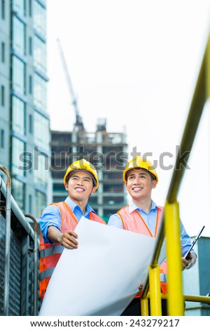Asian Indonesian construction workers with blueprint or plan on building site - stock photo