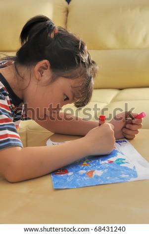 Asian kid drawing at home - stock photo