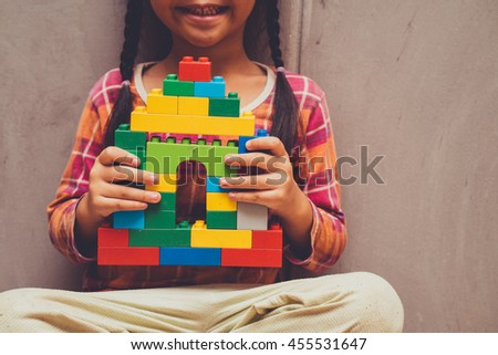 Asian kid girl holding house from plastic blocks and smiling in vintage tone - stock photo