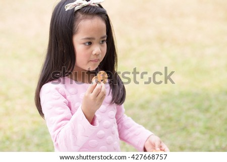 Asian kid girl offering a cookie - stock photo