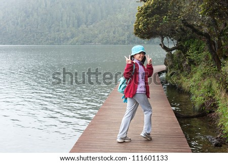 Asian kid hiking on the plank road in the park - stock photo