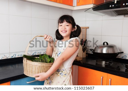 Asian kid holding a basket full of vegetables in the kitchen - stock photo
