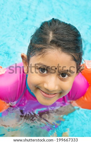 Asian kid in swimmer class with float bands. Indian child learning swimming in pool. - stock photo