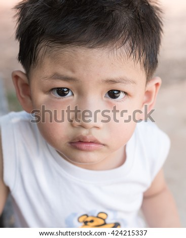 Asian kid with natural loose tooth.selective focus. - stock photo