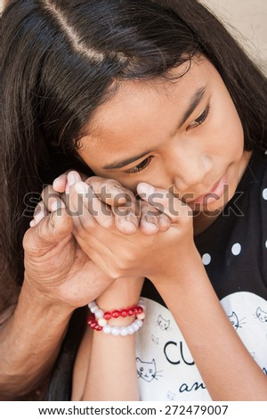 asian kids little girl  hand touches and holds an old man wrinkled hands at face of her - stock photo