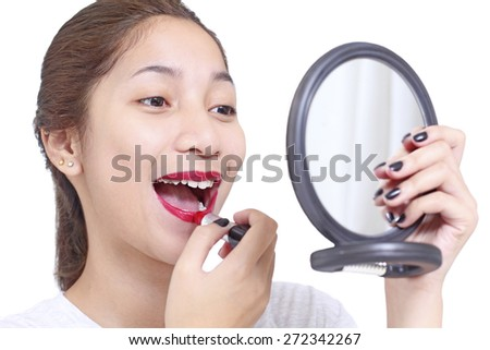 Asian lady looking into a mirror while applying lipstick. Isolated in white background. - stock photo