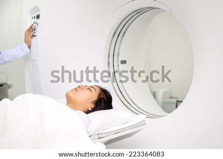 Asian lady sleep on a CT Scan bed and panel control by Radiologic technician - stock photo