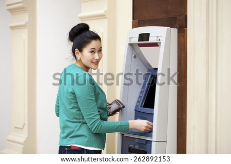 Asian lady using an automated teller machine . Woman withdrawing money or checking account balance - stock photo