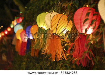 Asian lanterns on vine fence - stock photo