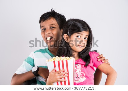 asian little boy and girl watching movie with pop corn, little indian girl sitting with brother watching movie eating popcorn, indian kids eating pop corn, kids watching movie with pop corn - stock photo