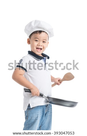 Asian little boy dressed  in a suit of the cook like a chef making diner - stock photo