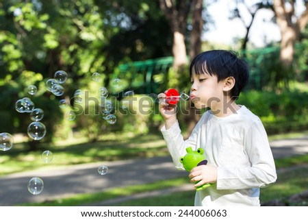Asian little boy is blowing a soap bubbles in park - stock photo