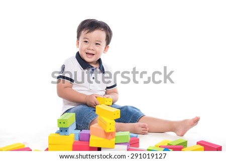 Asian little boy playing with construction blocks over white background - stock photo