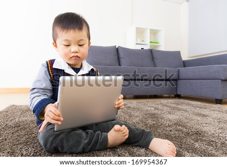 Asian little boy using tablet at home - stock photo