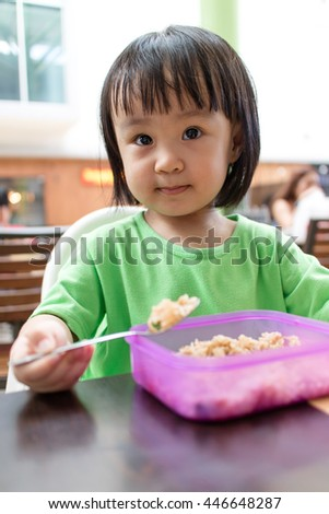 Asian Little Chinese Girl Eating Fried Rice in Outdoor Cafe - stock photo