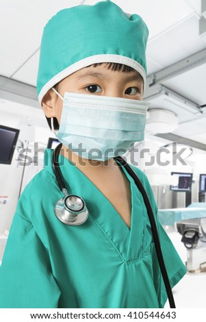 Asian Little Chinese Girl Playing a Doctor with Mask and Stethoscope  in Surgery Room - stock photo