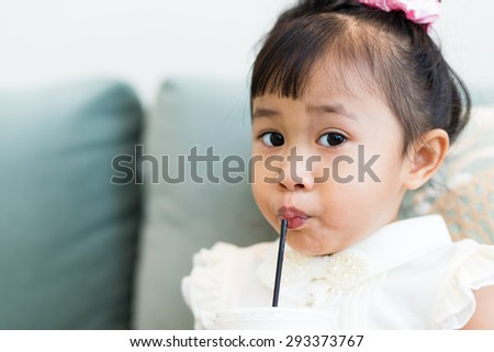 Asian little girl drinking with straw - stock photo