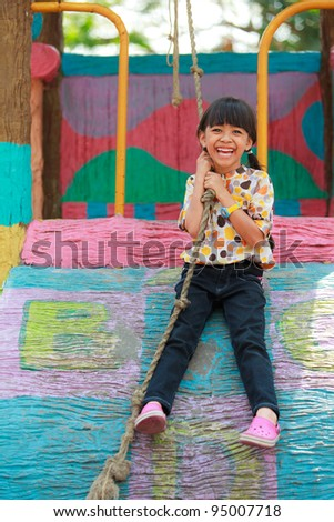 Asian little girl enjoys playing in a children playground - stock photo