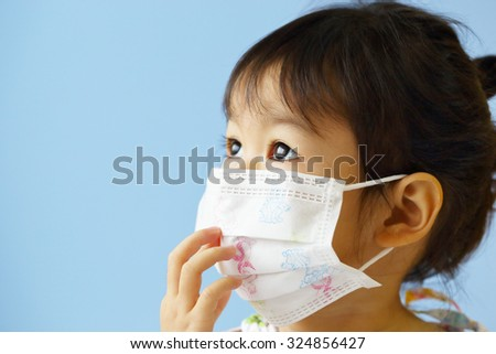Asian Little Girl Gets Sick on Blue Background. - stock photo