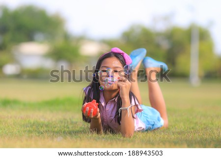 Asian little girl is blowing a soap bubbles. - stock photo