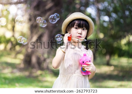 Asian little girl is blowing a soap bubbles with smile face in park - stock photo