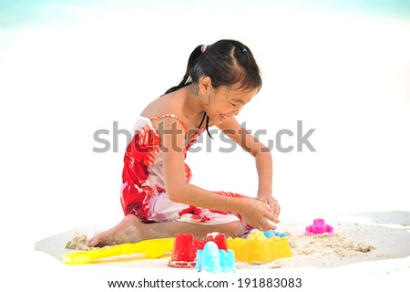 Asian little girl playing on the beach - stock photo