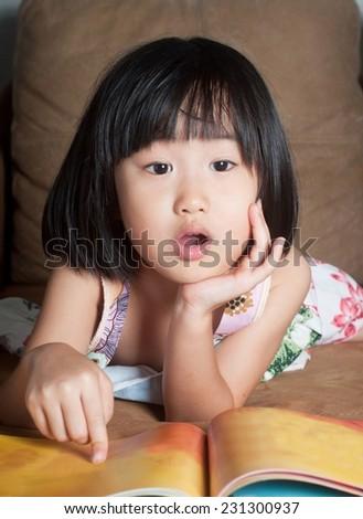 Asian little girl read her book aloud.Shallow DOF - stock photo
