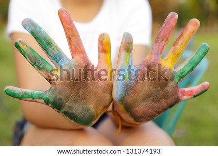 Asian little girl with hands painted in colorful paints - stock photo