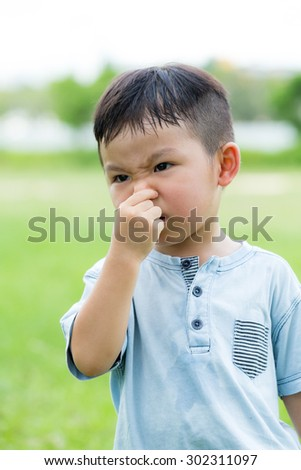 Asian little kid feeling itchy on his nose - stock photo