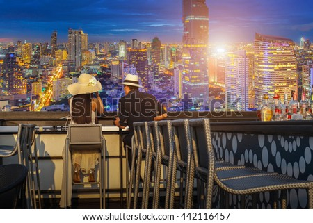 Asian lover couple enjoying look at view twilight time on top view bar and restaurant in this time beautiful colorful night at Bangkok City - stock photo