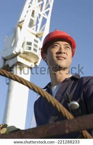 Asian male construction worker wearing hardhat - stock photo