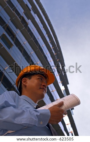 Asian male in a hard-hat holding some floor plans on his way out to a construction site - stock photo