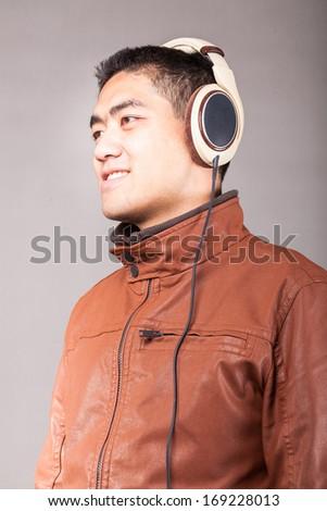 asian male listen to the headphones studio shot - stock photo